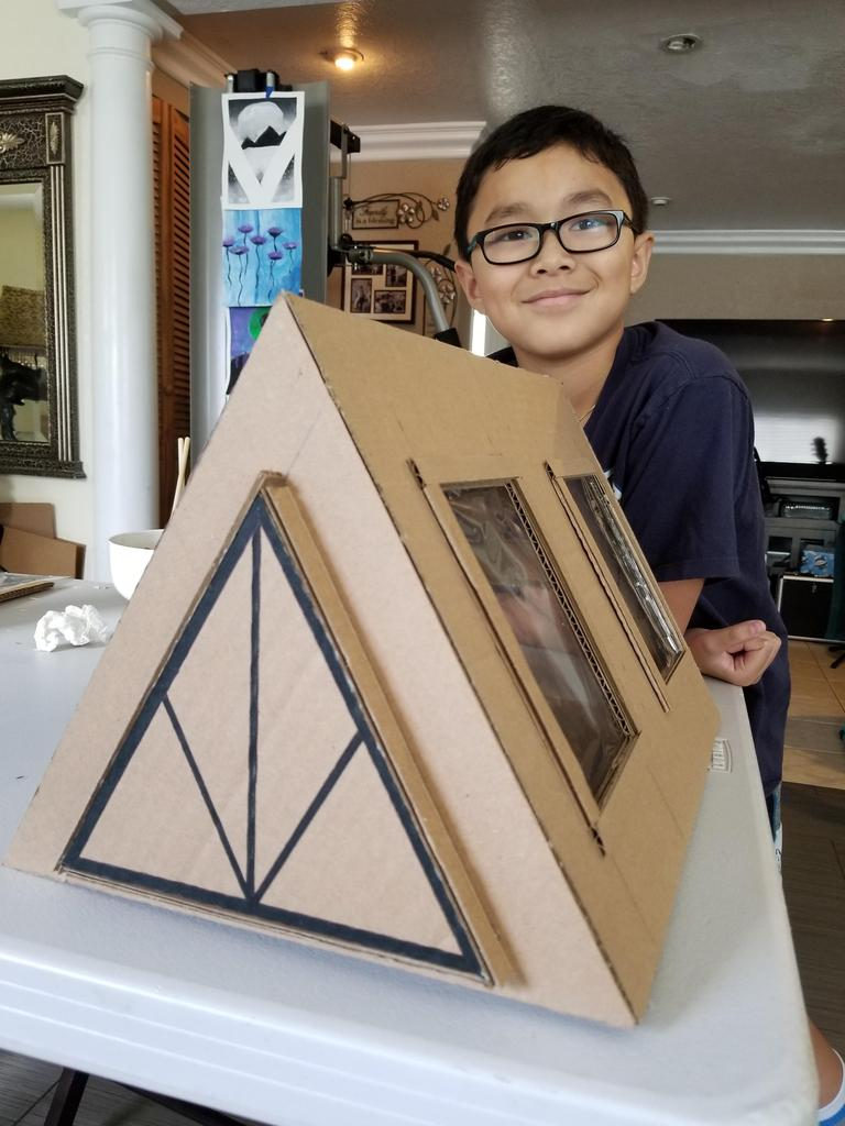 A framed house made out of cardboard with student in picture