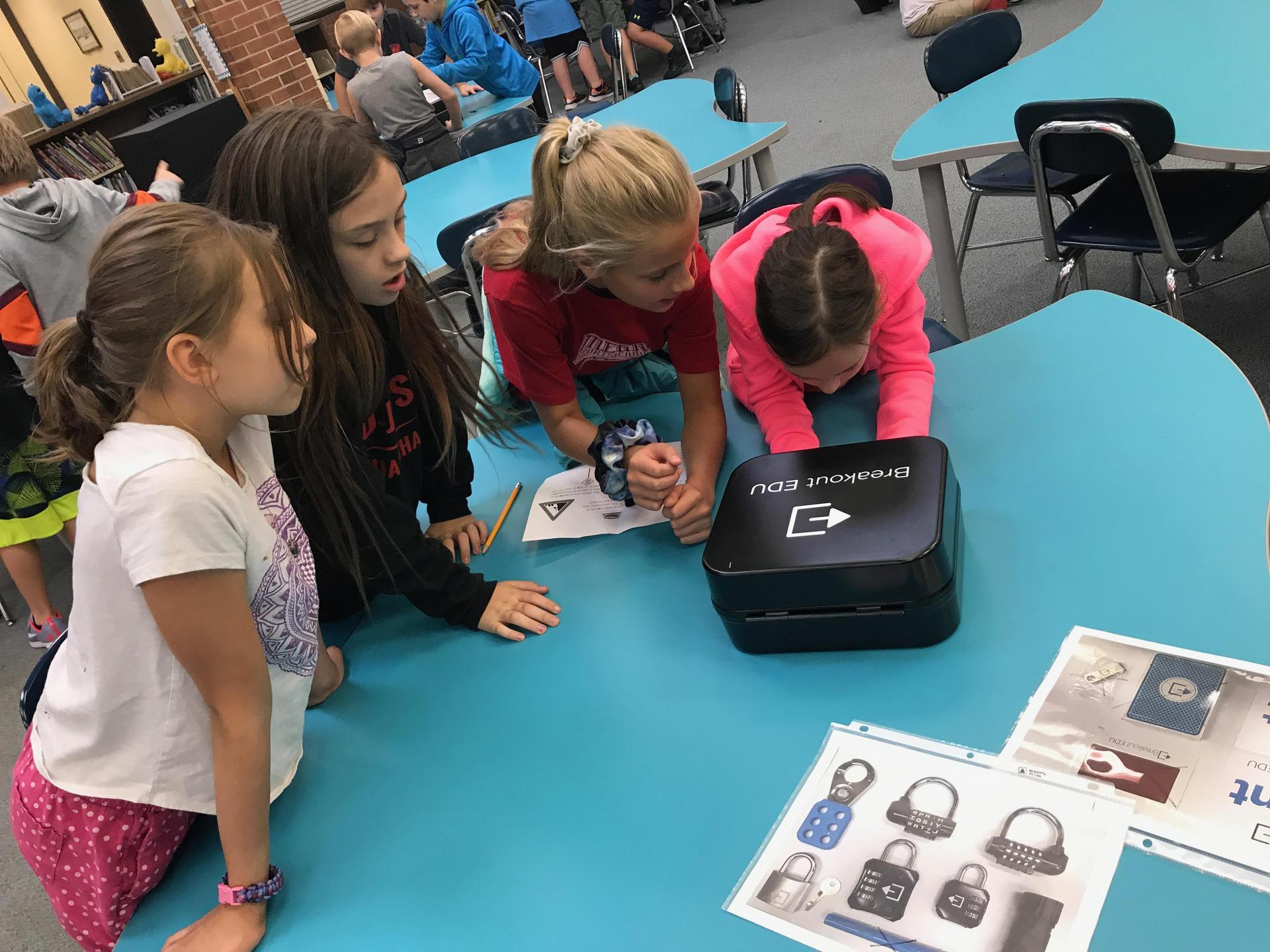 Image of students gathered around breakout boxes