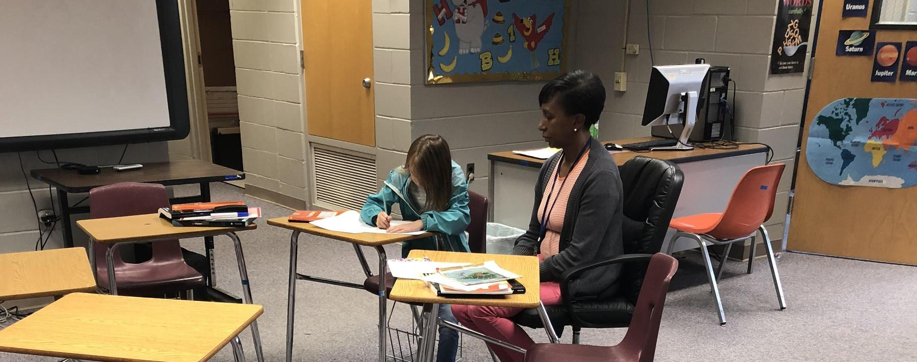 Ms. Cunningham helping student with work.