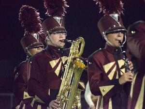 William Gutierrez plays saxophone during football halftime show.