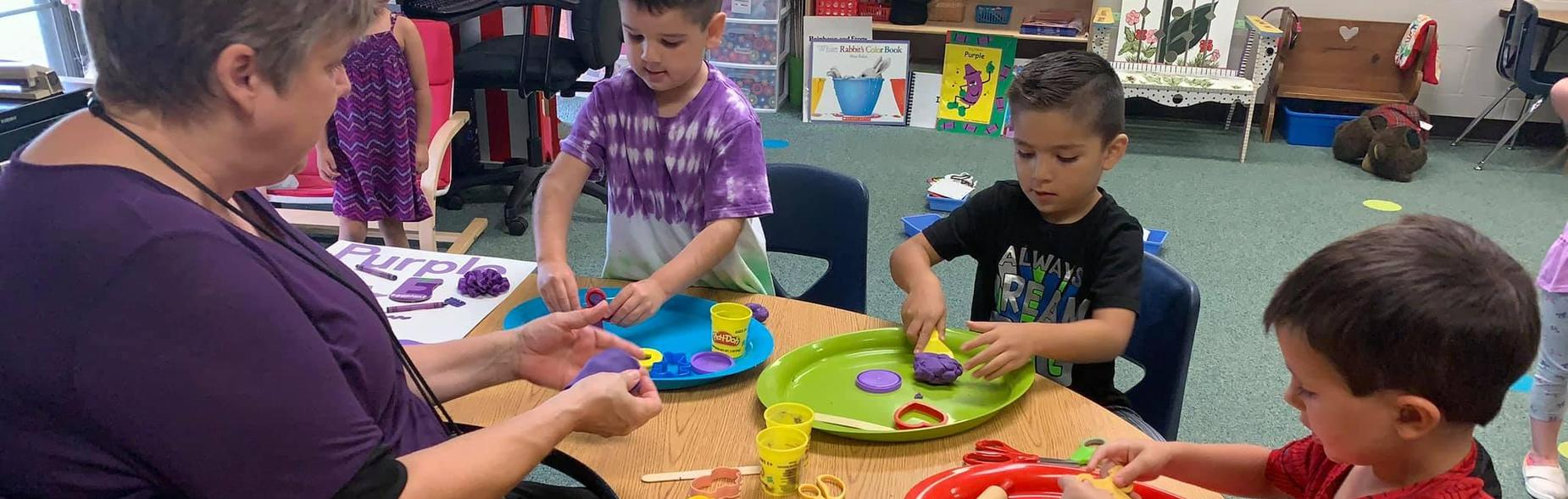 teacher and students using playdoh