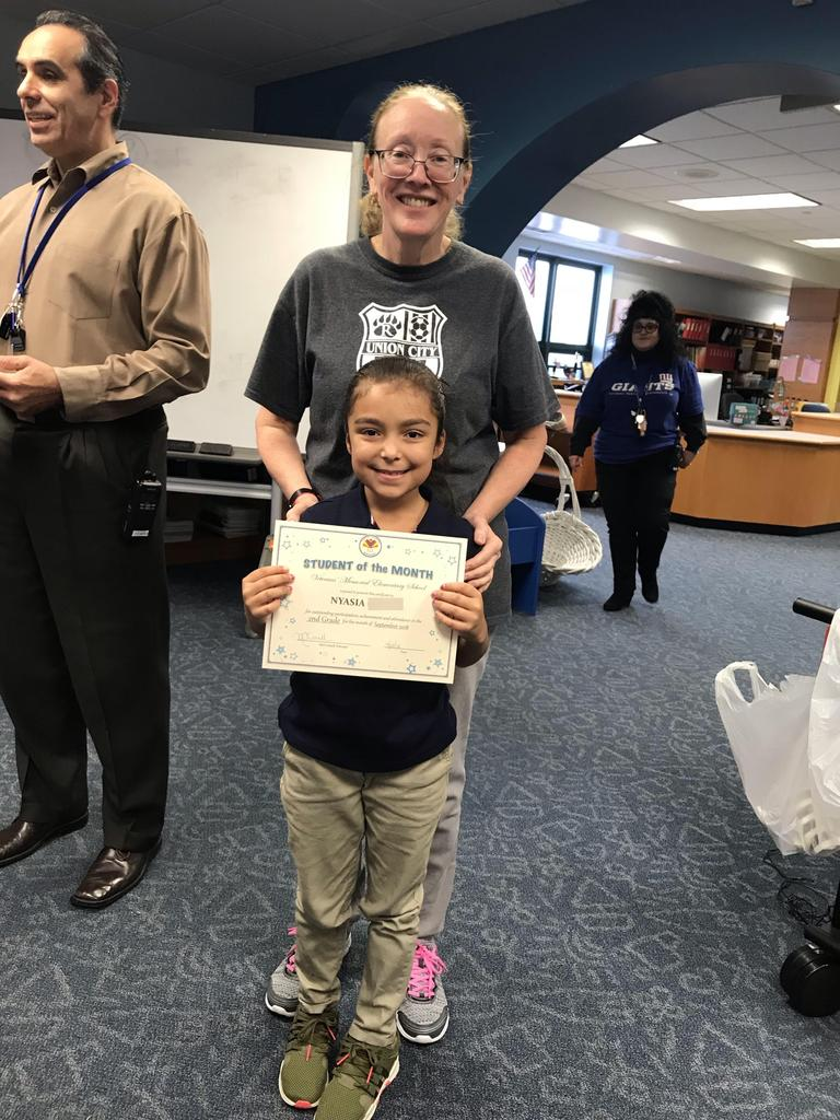 student of the month Nyasia grade 2 with principal O'connel