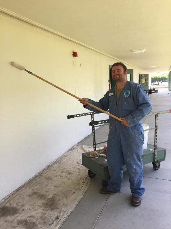 Man painting school hallway