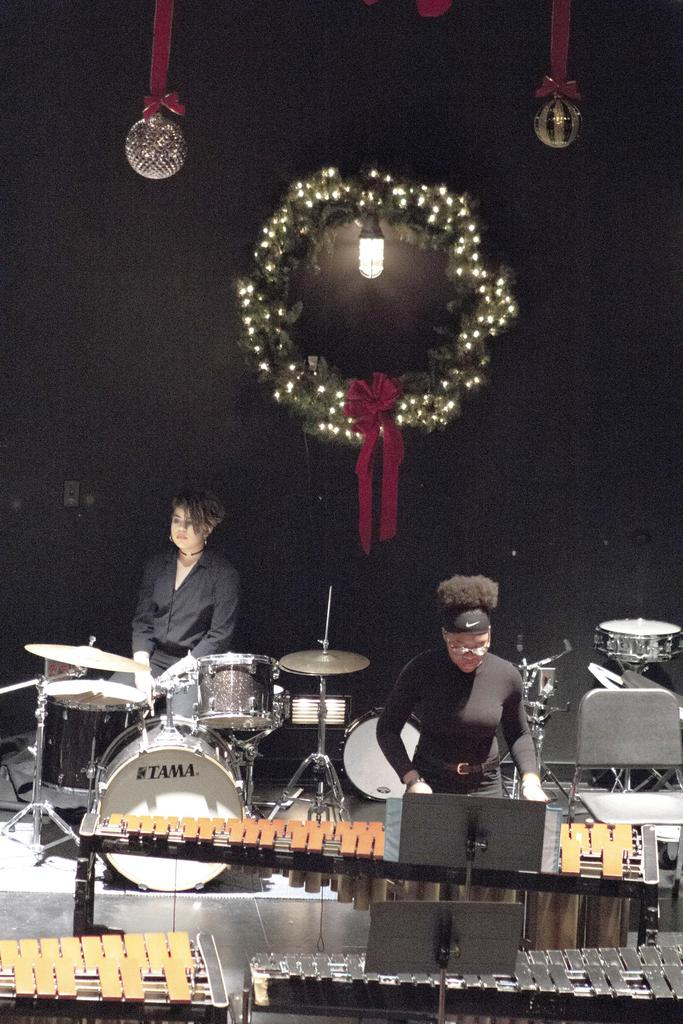 A vertical photo of two members of the percussion ensemble in front of a large wreath with lights