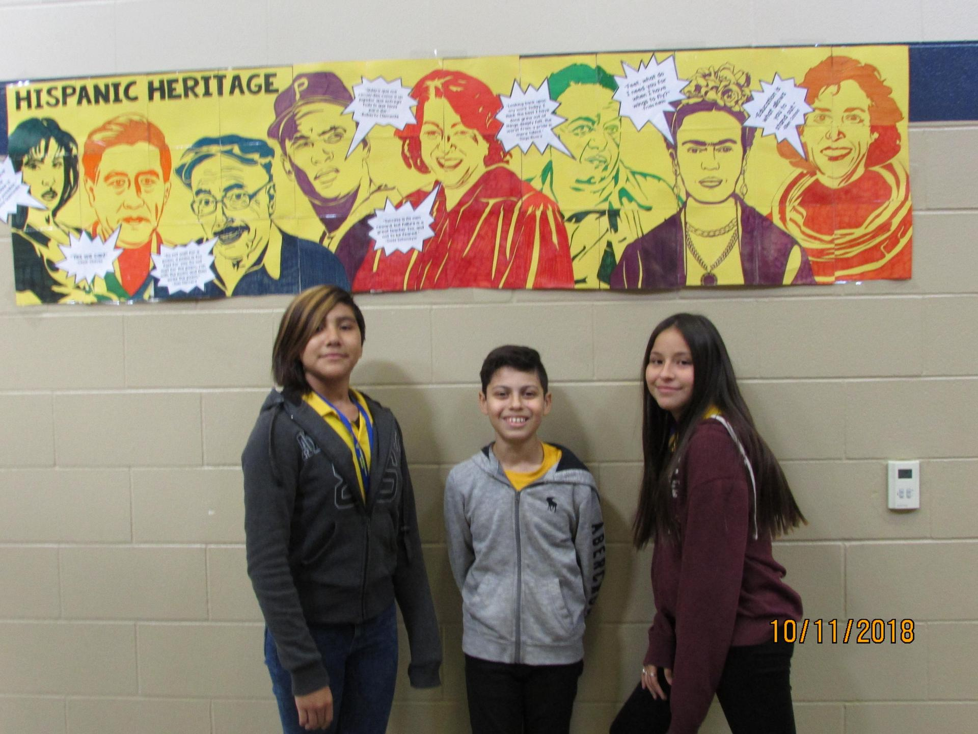 Students standing in front of Hispanic Heritage Collaboration poster.