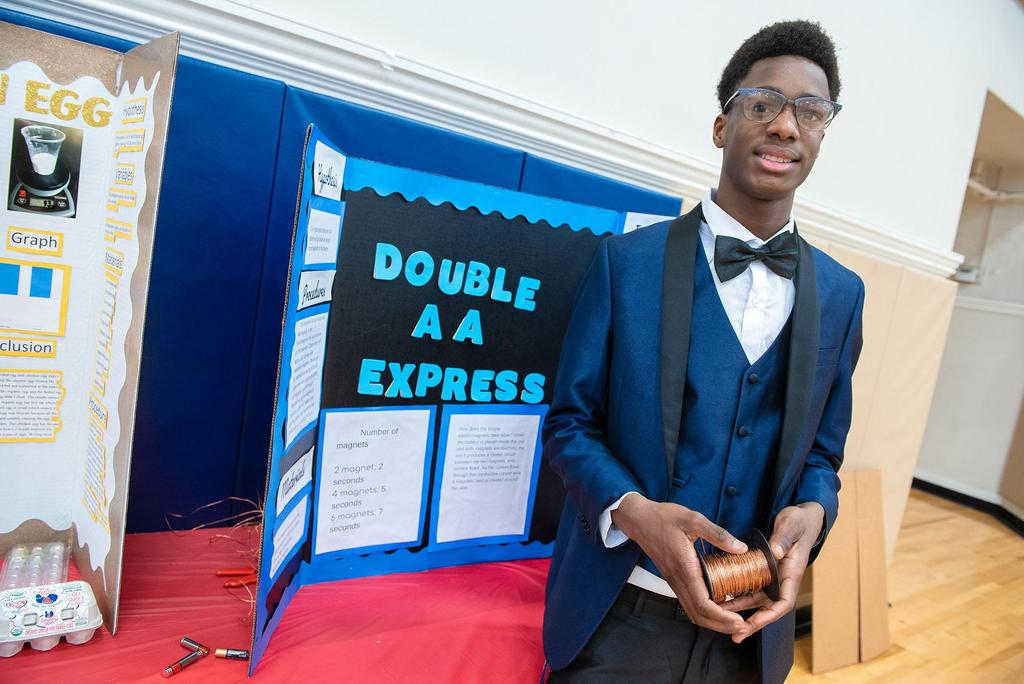 A student in a bowtie and a suit stands in front of his project
