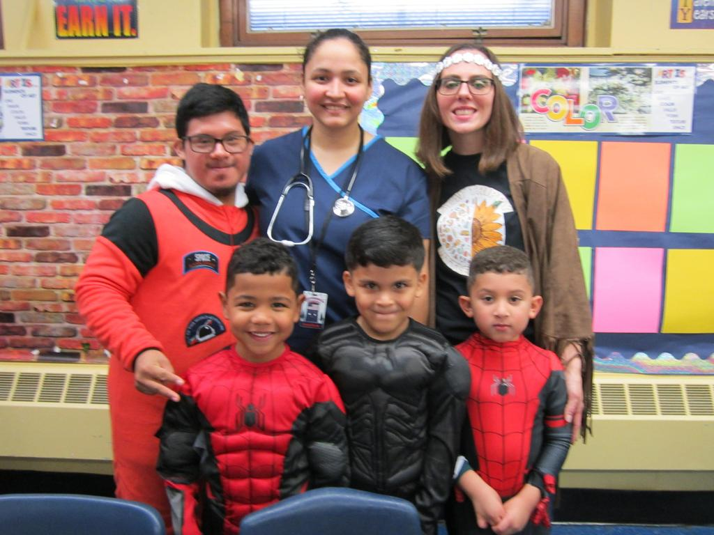 male student, art teacher ms. cintron, ms. viera and three little boys smiling