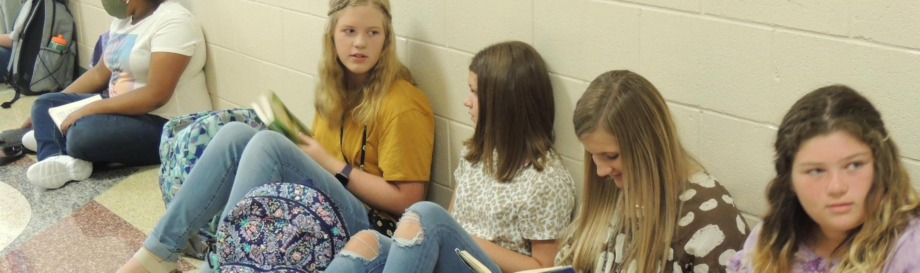 8th graders reading in the hallways before school