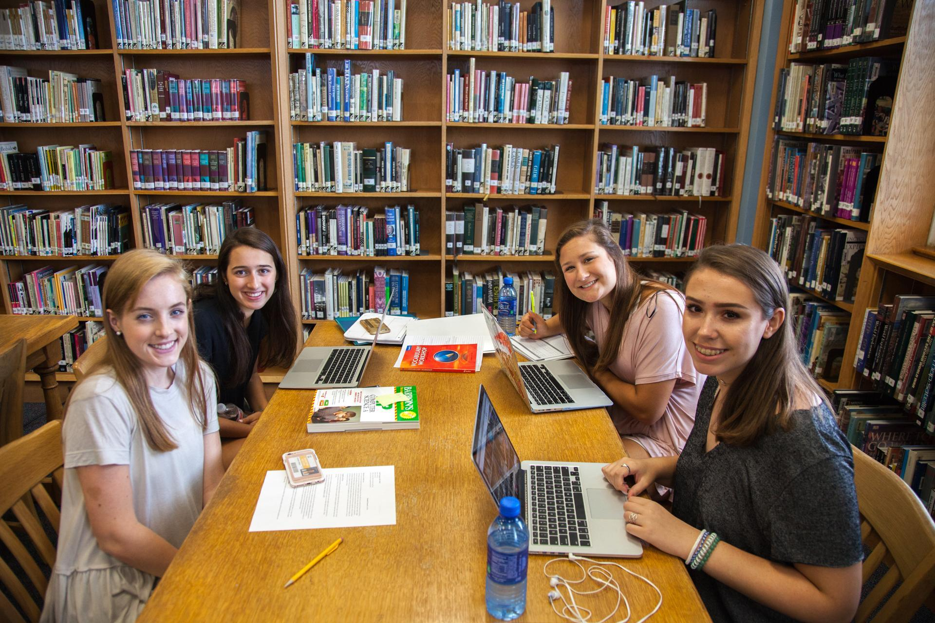 Four HPHS students gather around their laptops in the library to work on classroom assignments.