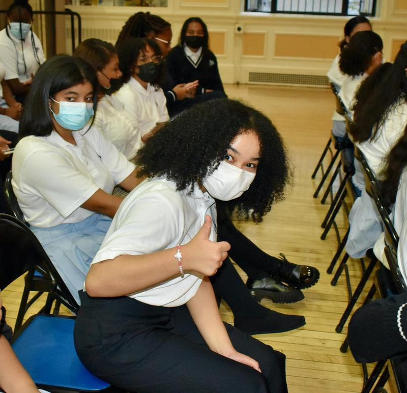 girl in white mask with curly hair giving a thumbs up sign