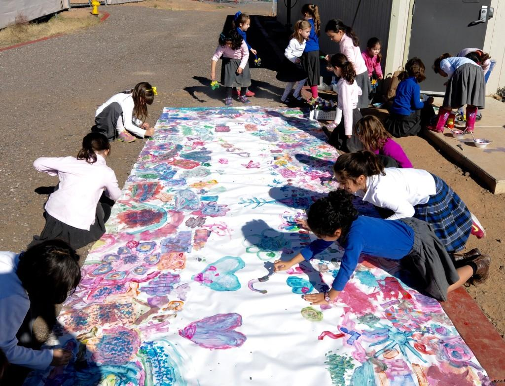 Girls creating a colorful mural outside