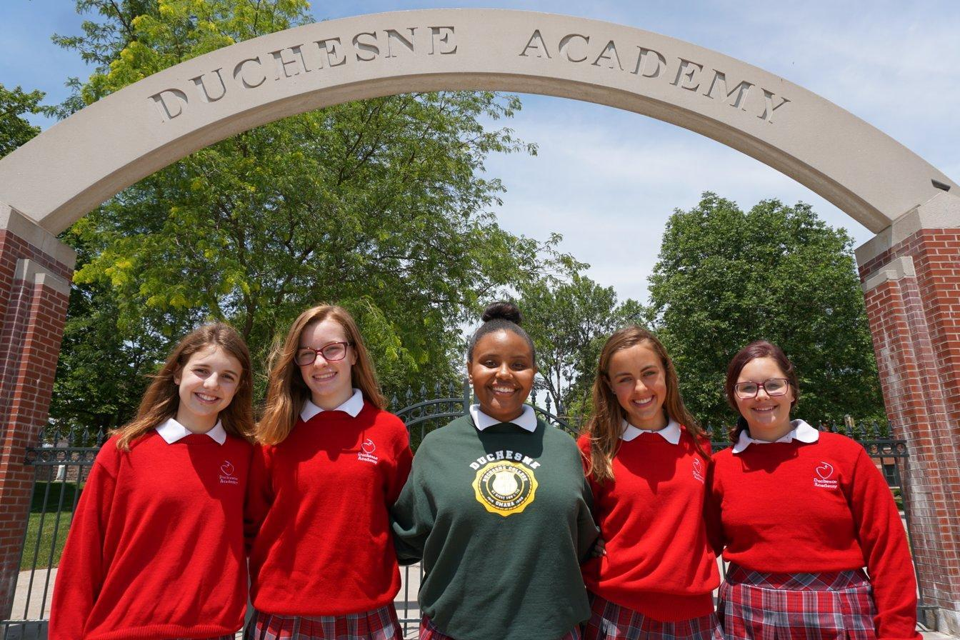 Students in front of Duchesne Academy sign