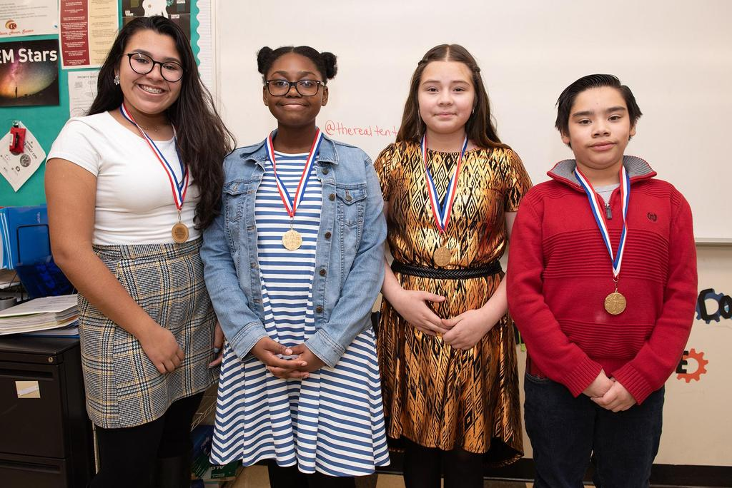Four students wearing their honorable-mention medals