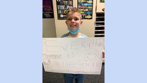 boy holding sign that says everything is awesome