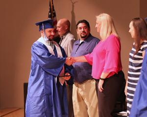 Hemet Adult School student shakes hands with Assistant Principal at the Summer School Graduation Ceremony.