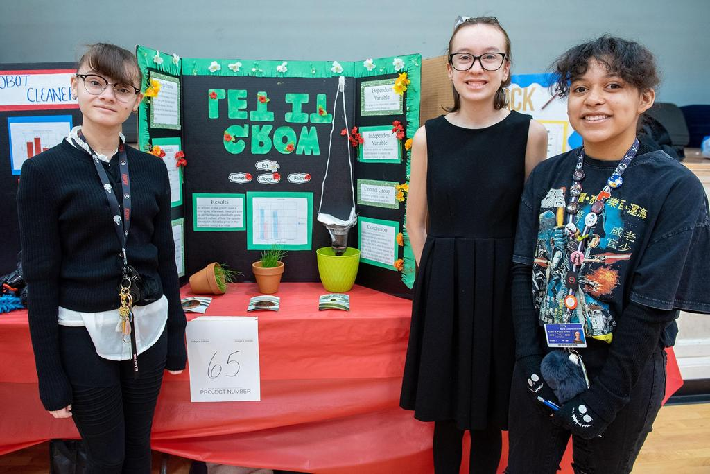 Posed photo of three students with their project