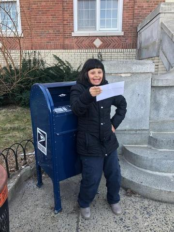 girl holding letter in her hand in front of mail box