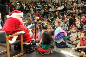 students sitting on the floor around Santa as he reads them a story