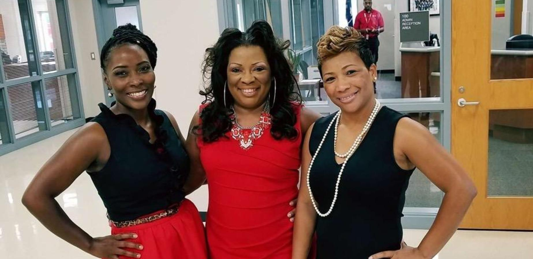 3 ladies wearing red and black to support education.
