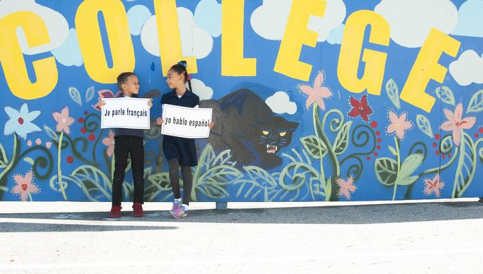 French and Spanish immersion students in front of school mural