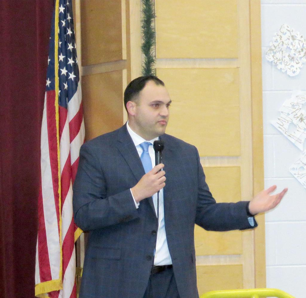 Assistant Principal Paolo Lambresa extends an arm toward the audience as he speaks at a microphone