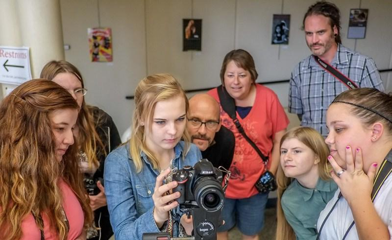 Students learn photography during a hands-on demonstration.