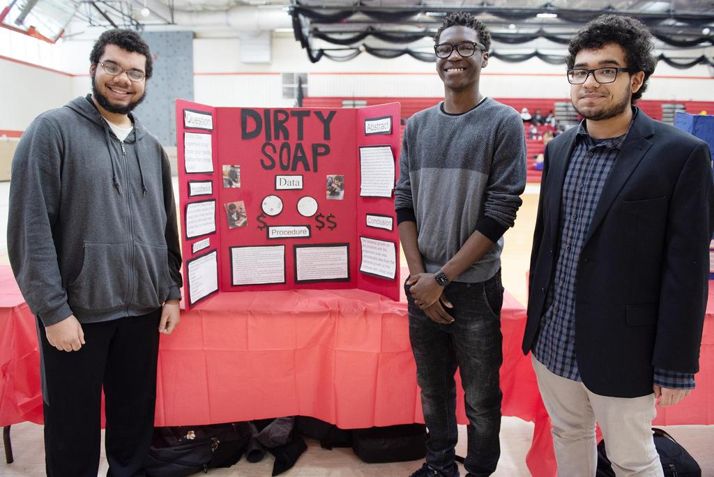 Three students stand in front of a project called Dirty Soap