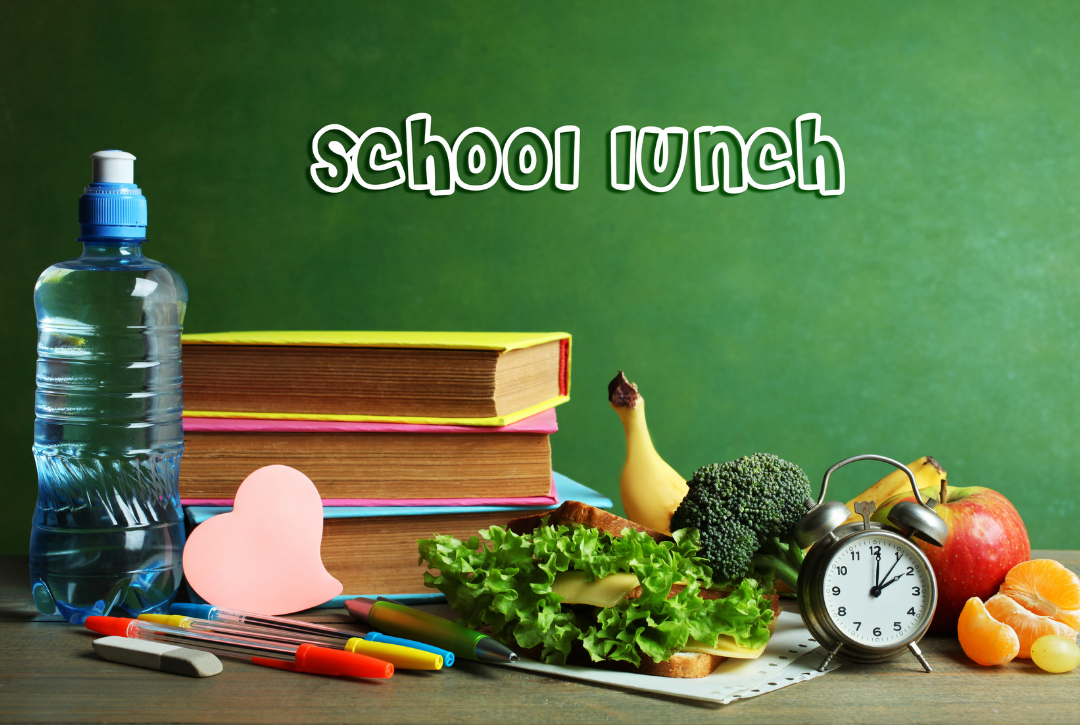 school lunch written on board with books and lunch items in foreground on desk