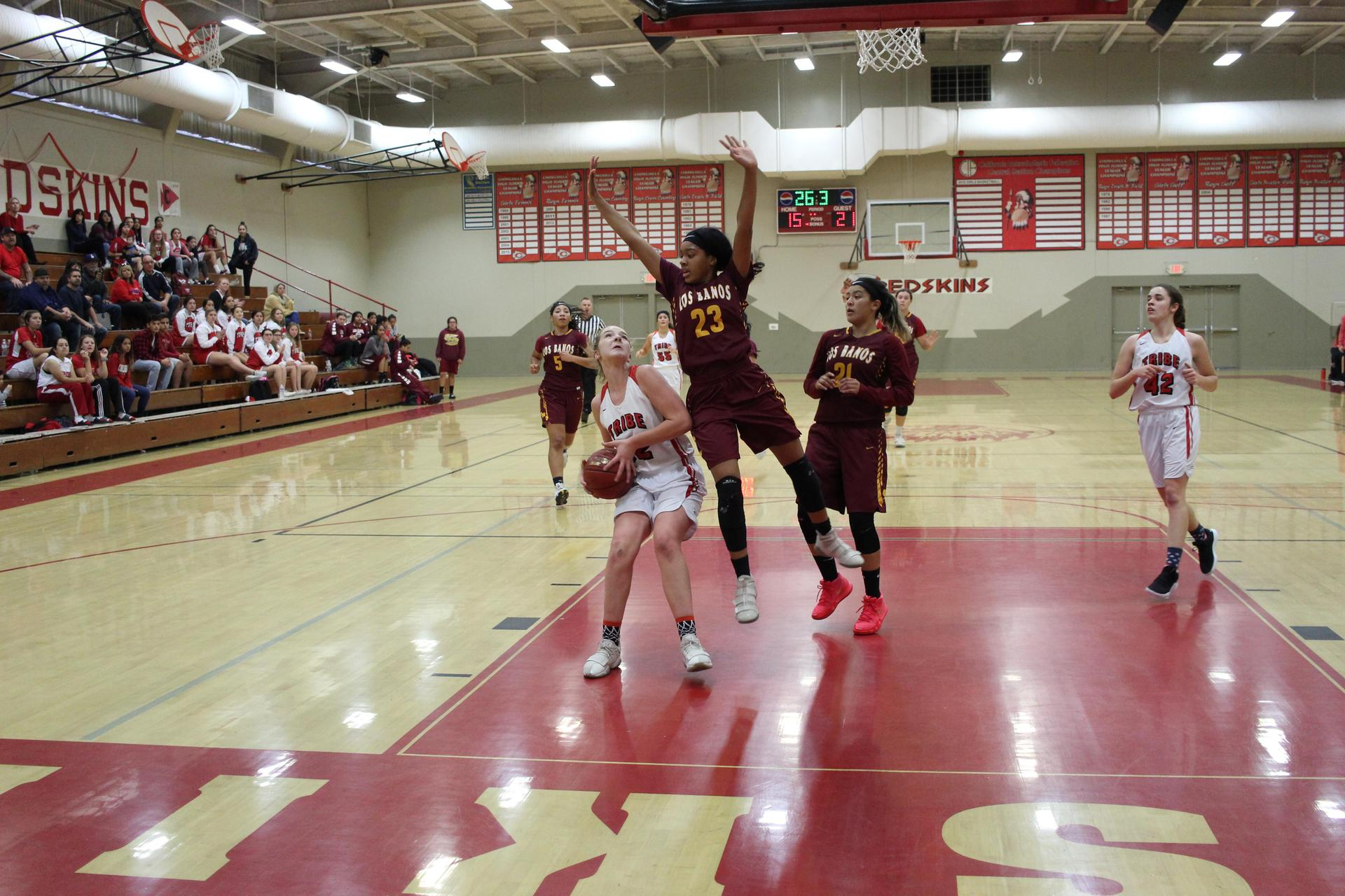 Varsity girls playing basketball against Los Banos