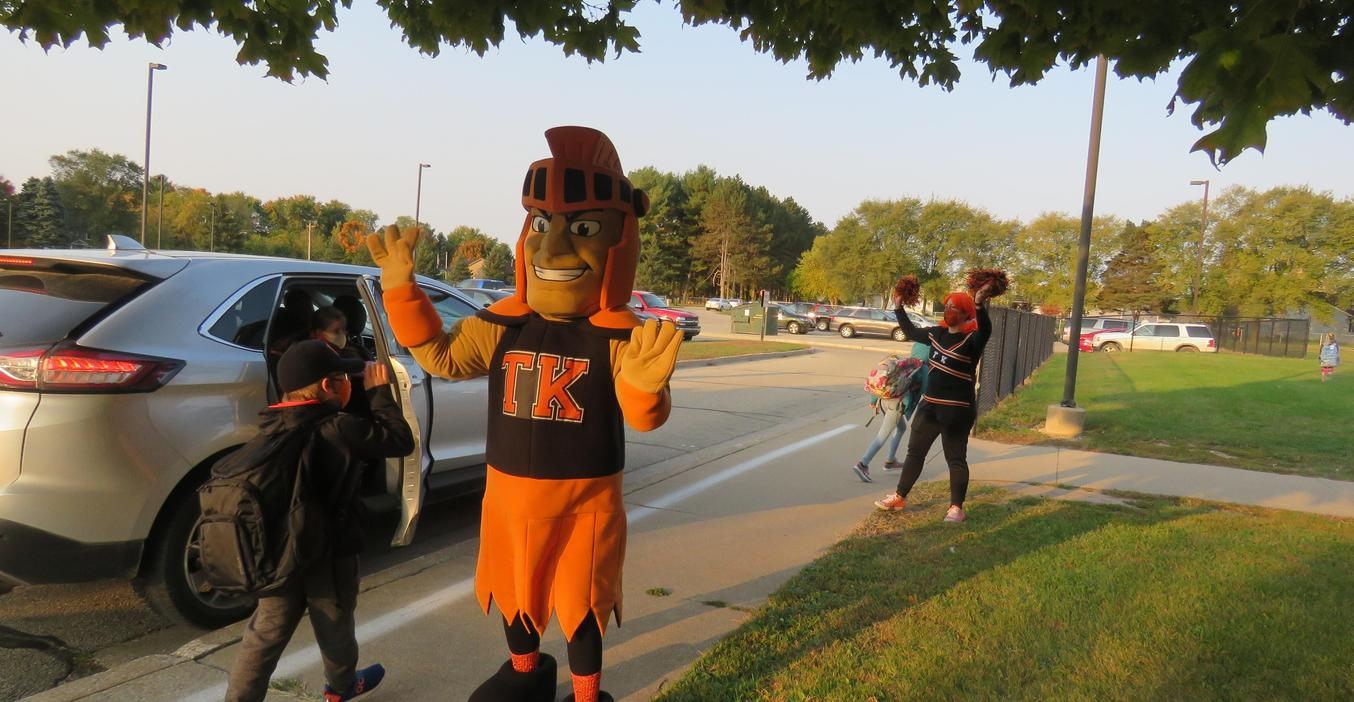 Tommy Trojan and a cheerleader greet students on TK Spirit Day.