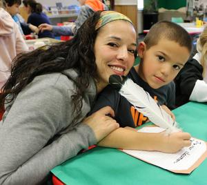 2nd grader tries his hand at calligraphy during Colonial Days at Wilson School.  Pictured here with his mom.