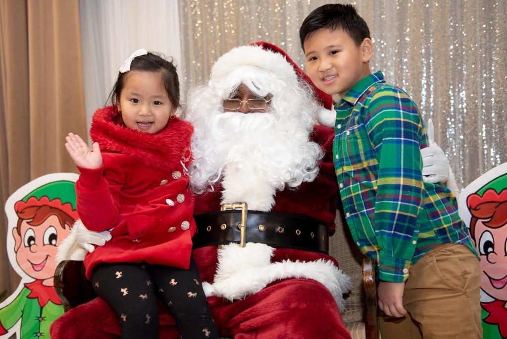 Two students on either side of Santa Claus