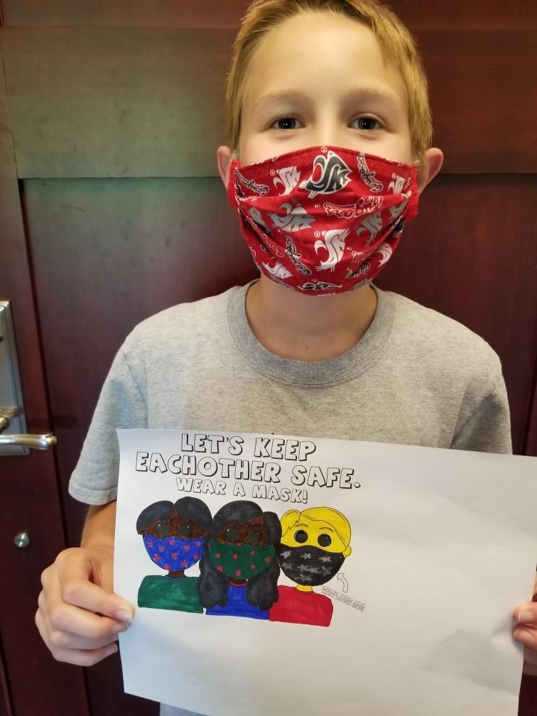 Young boy wearing WSU mask holding coloring page