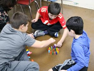 Three students work together to build a domino chain reaction during McKinley School's 6th Annual STEAM Night on Jan. 24.