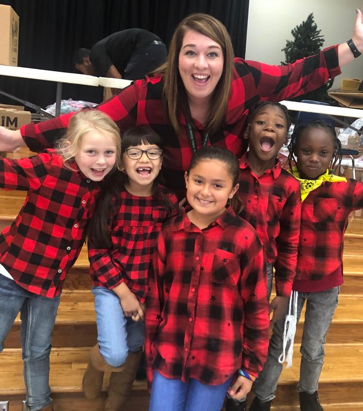 principal poses with 5 students in matching shirts