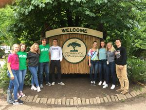 photo of a group of students in front of the sign for the Pittsburgh Zoo