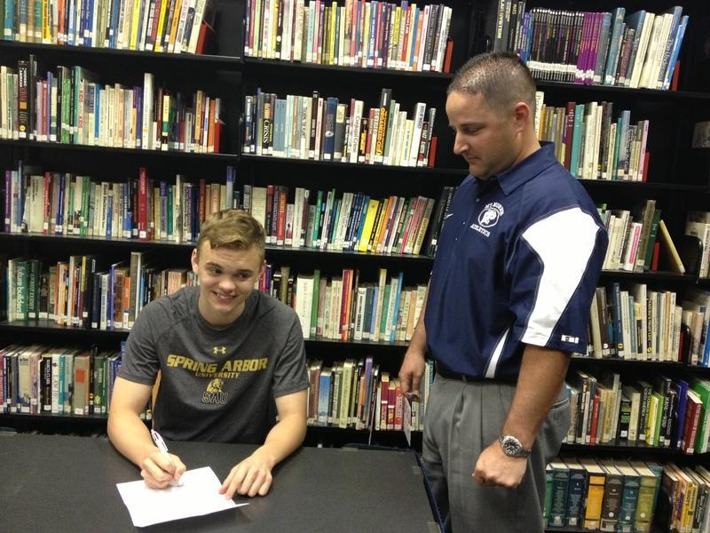 CJ Cameron signing his letter of intent to play soccer at Spring Arbor