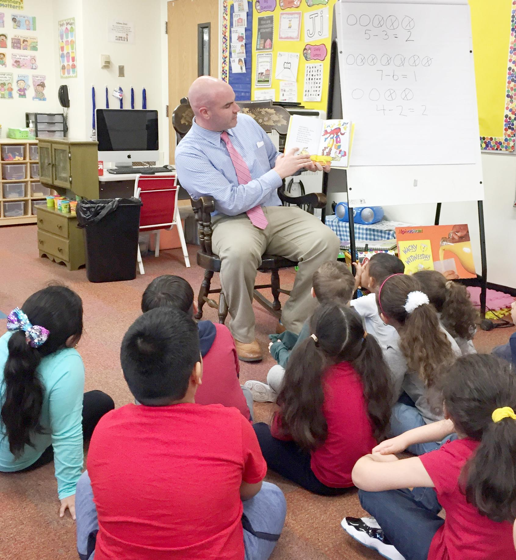 Educator reading to students, holding open a book