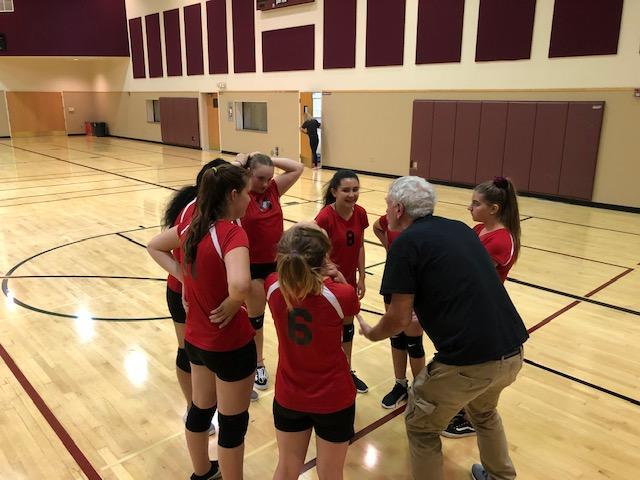 Girls Volleyball team having a quick check in with their coach.