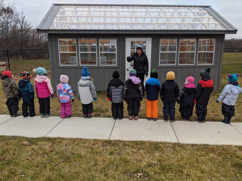 Mrs. B stands outside the green house with a class.