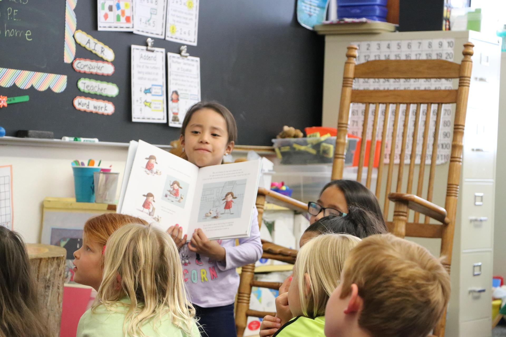 A student shares a picture book with classmates.