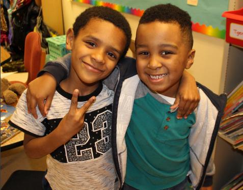 Two NBFA students hug and smile