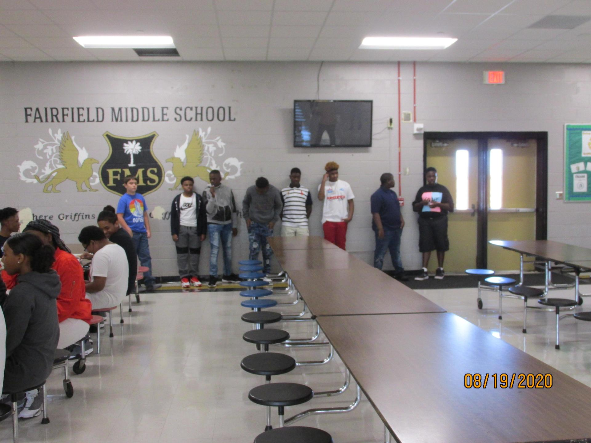 Students in line and sitting at tables in the cafe