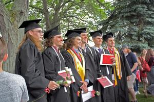 A line of graduates posing for a picture in black caps and gowns