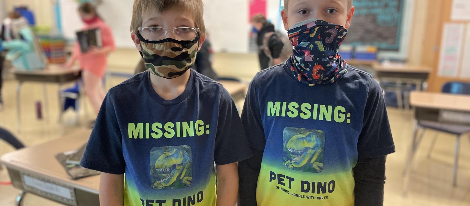 2 boys wearing matching shirts, wearing masks.