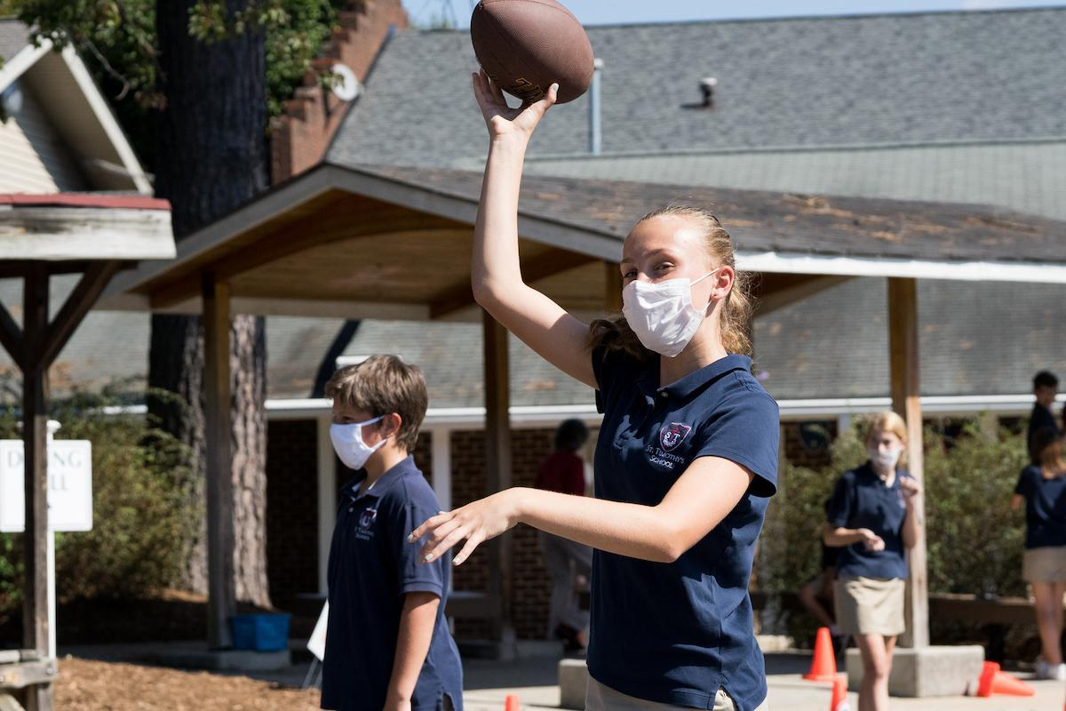 St. Timothy's School seventh grade girl throwing a football at recess
