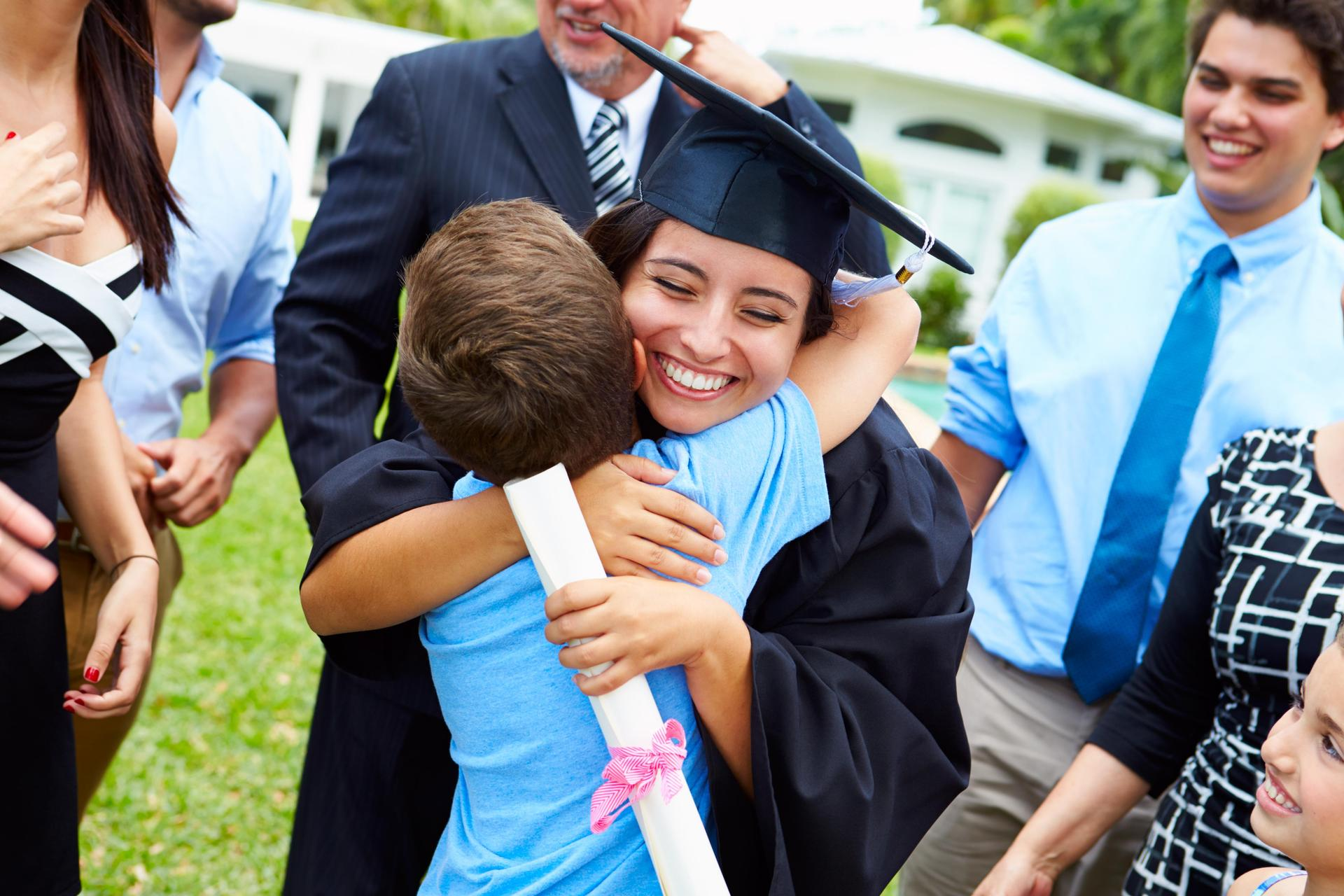 Proud graduate mom, hugging her son, smiling.