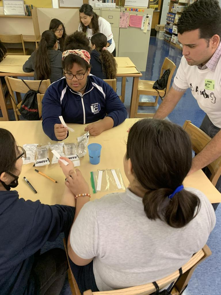 several groups of girls comparing their test strips with different solutions in a plastic bags