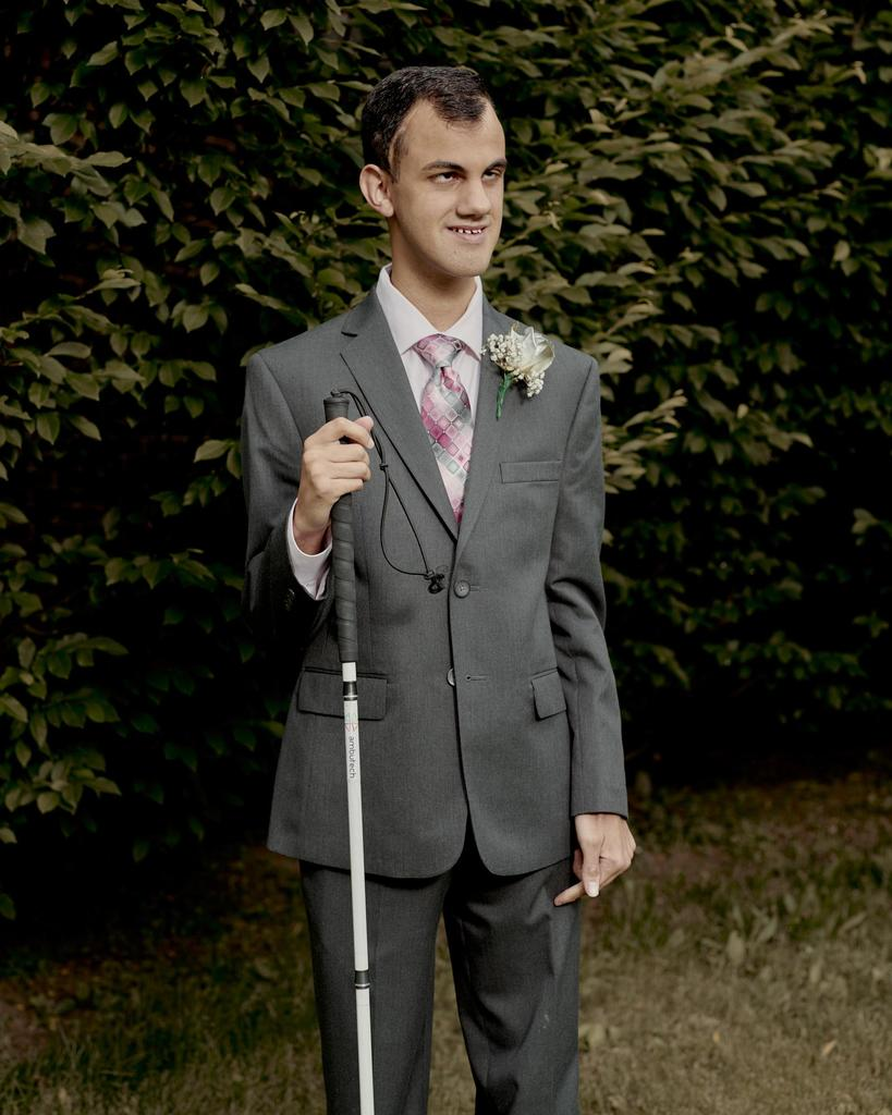 Anthony posing in sharp suit holding his cane.