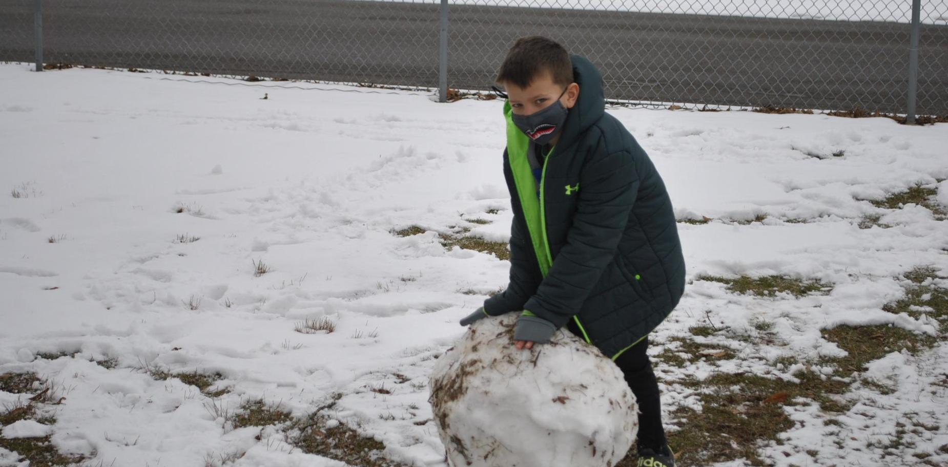student rolling snowball